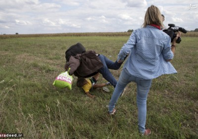 "A Syrian refugee, Osama Abdul Mohsen, carrying his youngest son Zaid falls after being tripped by TV camerawoman Petra Laszlo (R) while trying to escape from a collection point in Roszke village, Hungary, September 8, 2015. Osama Abdul Mohsen's story went viral after he was filmed being tripped up by a camerawoman as he fled police near the Hungarian border with Serbia last September. He was carrying his youngest son Zaid in his arms at the time, and the two fell sprawling on the ground. Footage of the incident helped bring him to the attention of a soccer training school in Getafe on the outskirts of Madrid, which found him work as a liaison officer. REUTERS/Marko Djurica/File Photo     SEARCH ""REFUGEE PEREZ"" FOR THIS STORY. SEARCH ""THE WIDER IMAGE"" FOR ALL STORIES   - RTX2CXD7"